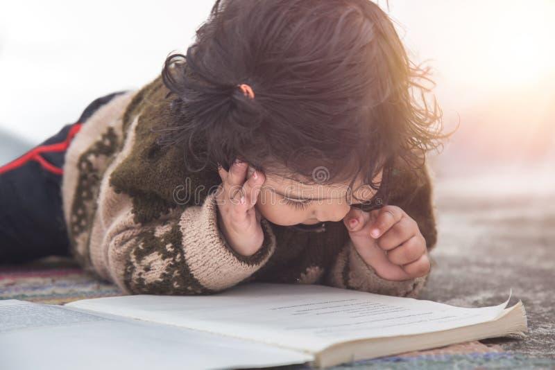 Ragazza del bambino cheimpara leggere dai libri, concetto di ispirazione di istruzione fotografie stock
