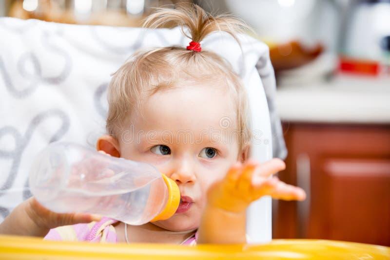 Ragazza del bambino con la bottiglia con la formula infantile sulla cucina fotografia stock