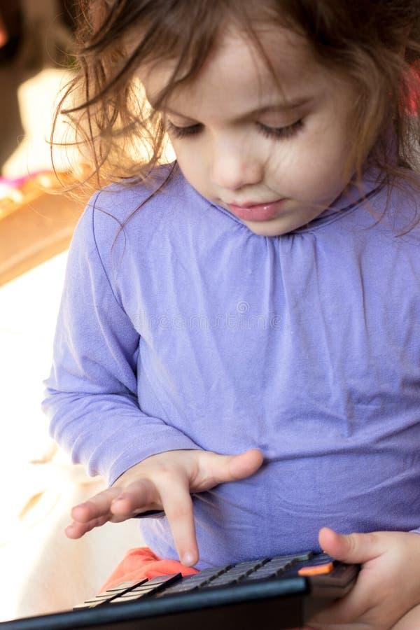 Ragazza del bambino con un calcolatore in mani fotografia stock