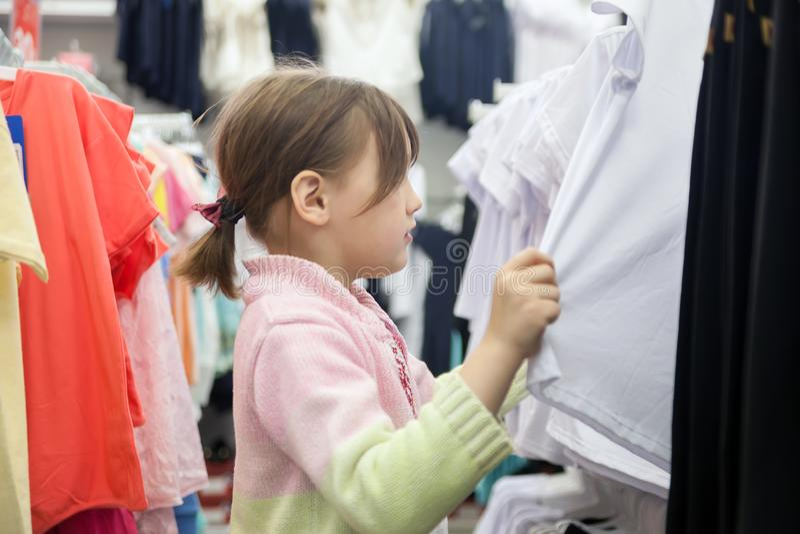 Ragazza del bambino di 7 anni nel negozio di vestiti dei bambini fotografia stock libera da diritti