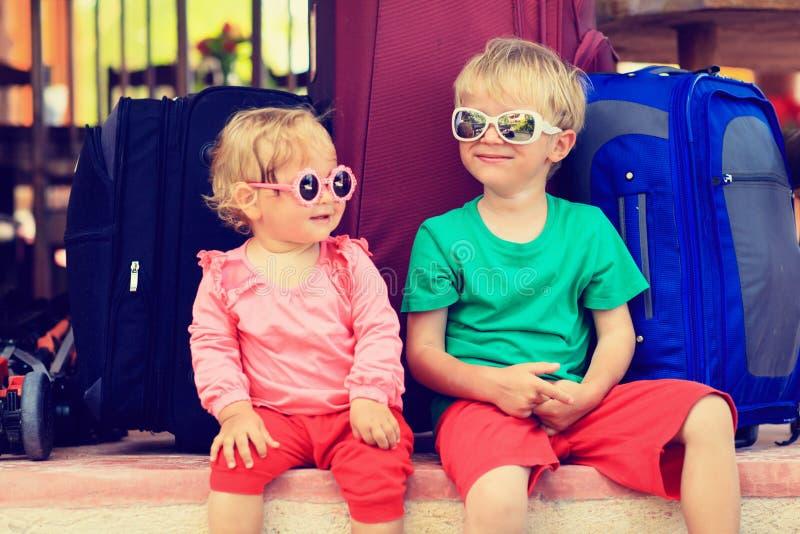 Ragazza del bambino e del ragazzino che si siede sulle valigie fotografie stock