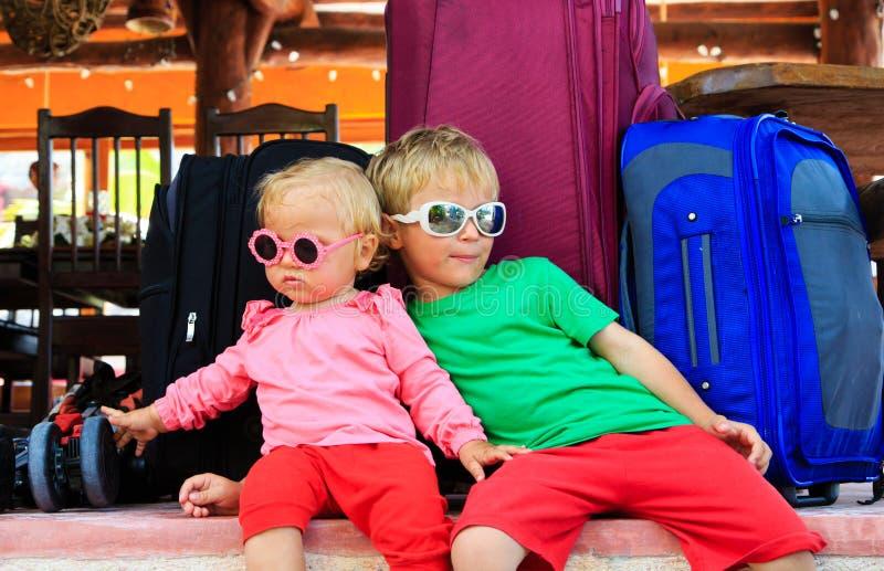 Ragazza del bambino e del ragazzino che si siede sulle valigie immagini stock libere da diritti