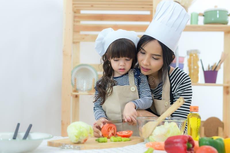 Ragazza del bambino e della madre che cucina e che taglia le verdure sulla cucina fotografia stock