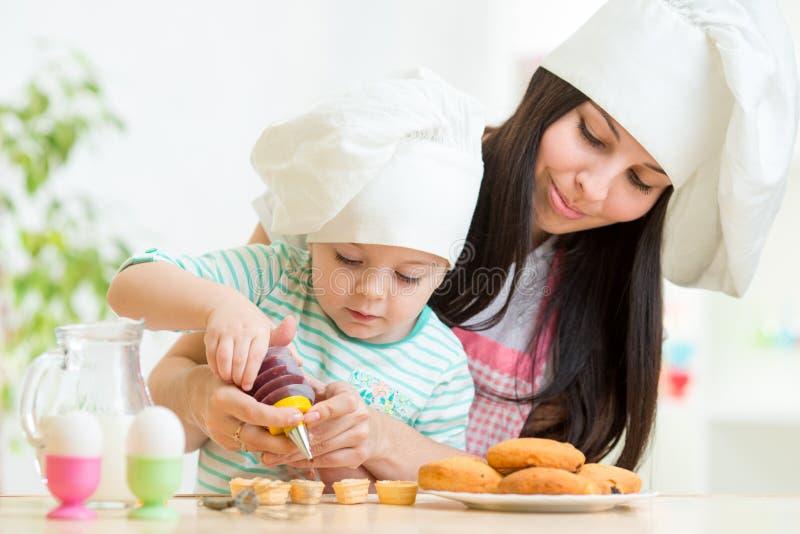 Ragazza del bambino e della madre che produce i biscotti fotografia stock