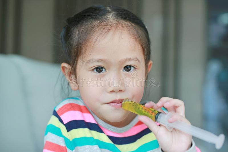 Ragazza del bambino del primo piano che si alimenta con la medicina liquida fotografia stock