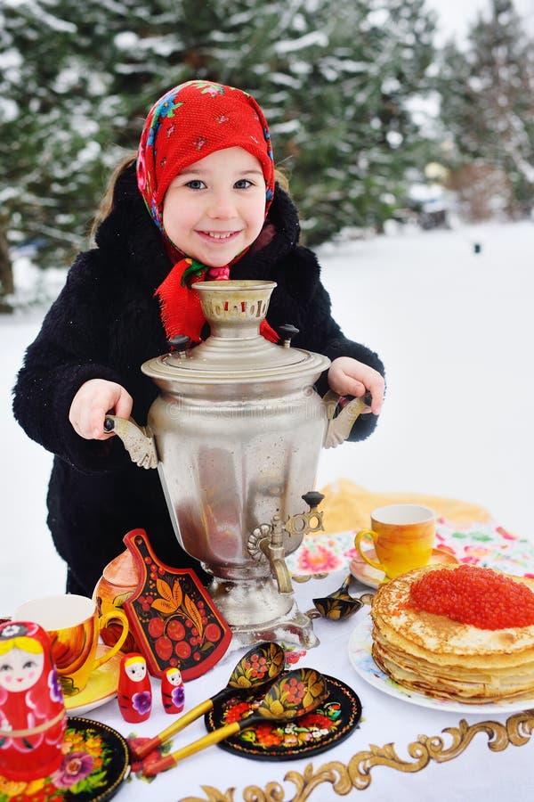 Ragazza del bambino in una pelliccia ed in una sciarpa nello stile russo che tiene una grande samovar nelle mani dei pancake con  fotografie stock