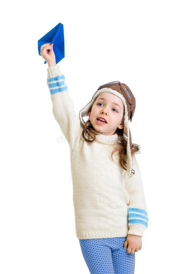 Ragazza del bambino vestita come il pilota e gioco con l'aeroplano di carta fotografie stock