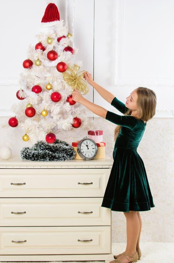 Ragazza del bambino vicino all'albero di Natale che aspetta orologio di mezzanotte Ultime preparazioni Il bambino celebra il nata fotografia stock libera da diritti
