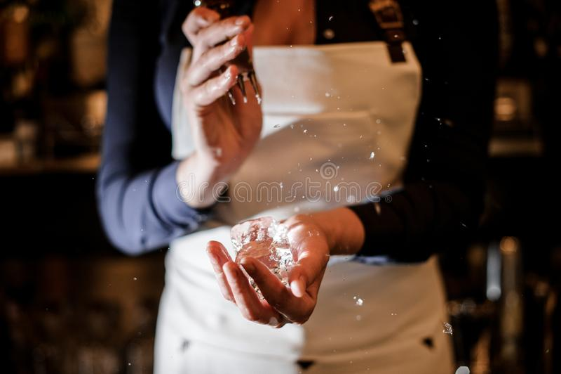 Ragazza del barista che schiaccia un pezzo di ghiaccio per la fabbricazione del cocktail fotografia stock libera da diritti