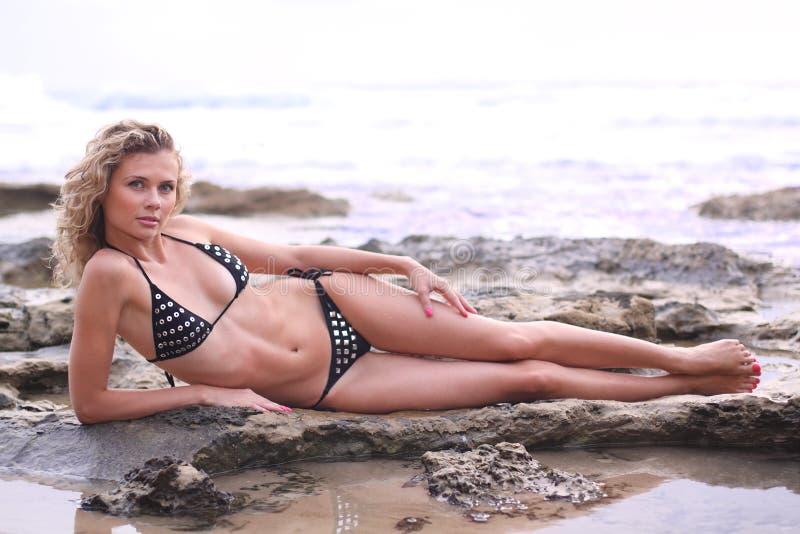 Ragazza del bikini che si trova su una roccia della spiaggia immagini stock libere da diritti
