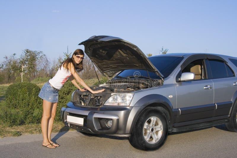 Ragazza del Brunette che ripara l'automobile fotografia stock libera da diritti