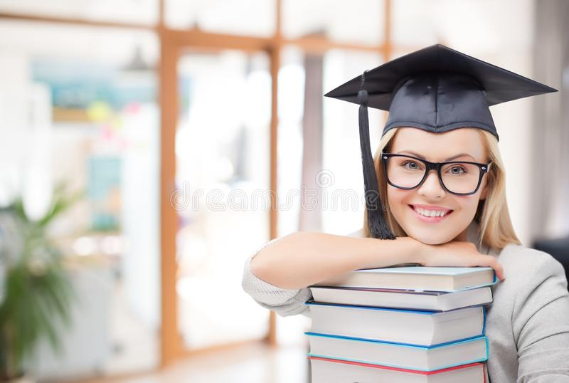 Ragazza del dottorando in cappello del celibe con i libri fotografia stock