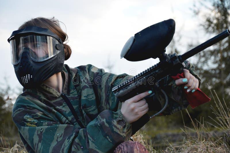 Ragazza del giocatore di sport di paintball nell'uniforme e nella maschera protettive del cammuffamento fotografie stock