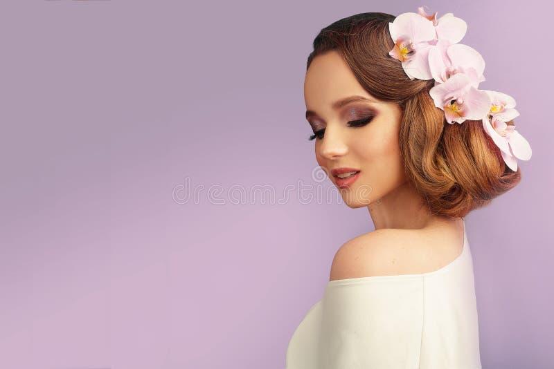 Ragazza del modello di estate di bellezza con stile di capelli variopinto dei fiori Bella signora con i fiori di fioritura su lei fotografie stock