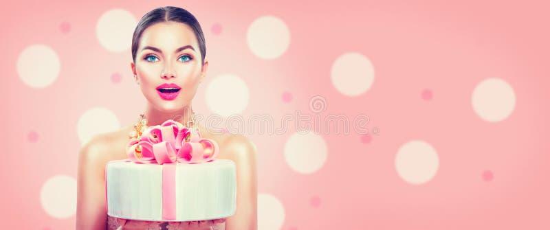 Ragazza del modello di moda che tiene bello partito o torta di compleanno su fondo rosa immagini stock