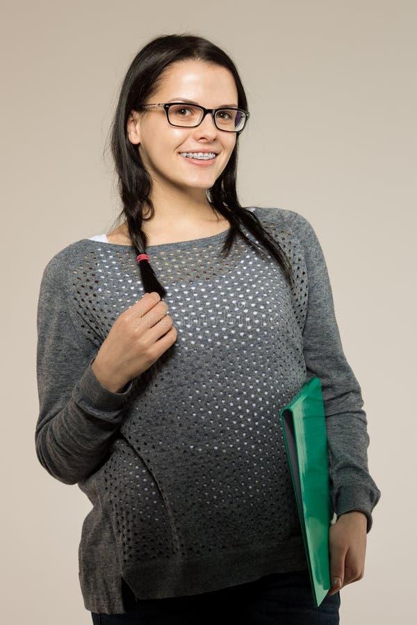 Ragazza del nerd in vetri e sostegni sui denti Pantaloni a vita bassa positivi e eccellenti della donna dello studente immagini stock