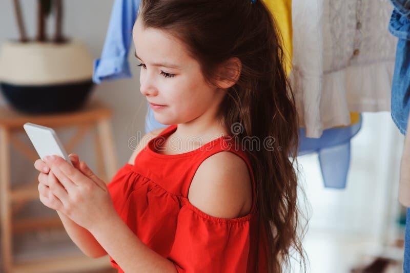 ragazza del piccolo bambino che fa selfie mentre provando sui nuovi vestiti nella sua stanza adatta del deposito o del guardaroba immagine stock