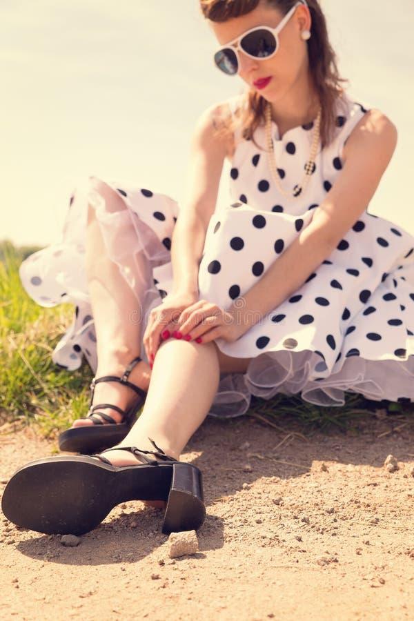 Ragazza del Pinup con il vestito bianco dall'isolatore a campana che aspetta sul bordo fotografie stock libere da diritti