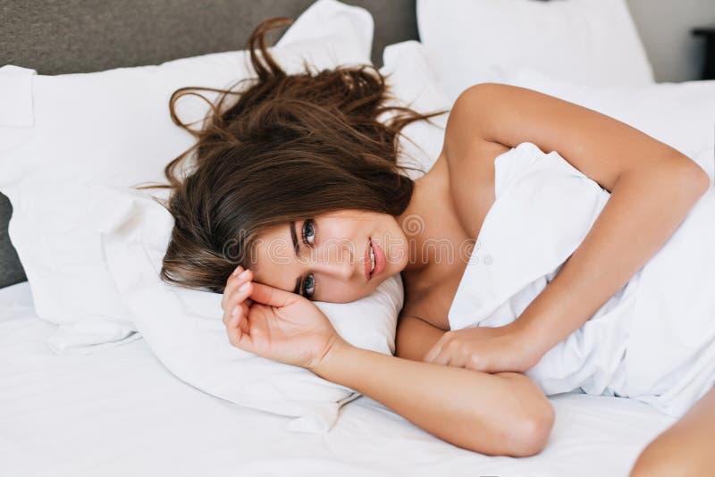Ragazza del ritratto sul letto in appartamento moderno di mattina Sta guardando alla macchina fotografica fotografie stock libere da diritti