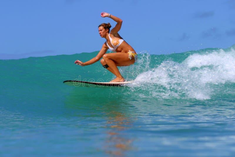Ragazza del surfista che pratica il surfing un'onda in Hawai fotografia stock