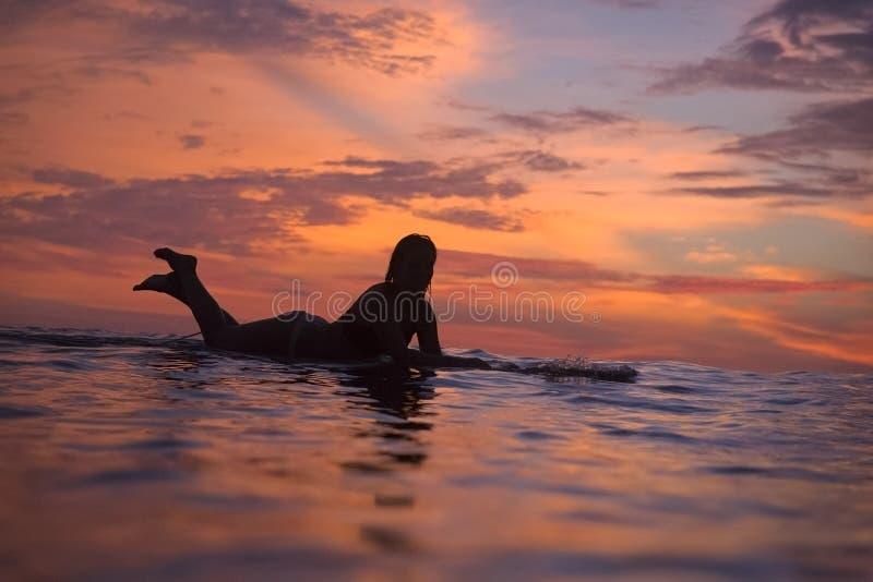 Ragazza del surfista in oceano a tempo di tramonto immagini stock