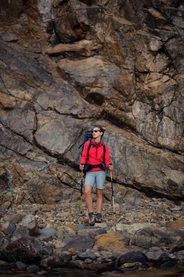 Ragazza del Trekker in occhiali da sole con lo zaino in montagne fotografie stock libere da diritti