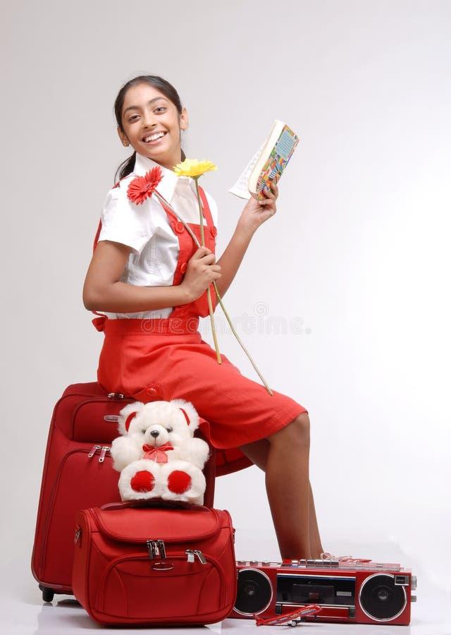 Ragazza del viaggiatore che si siede sui suoi bagagli con un libro fotografia stock libera da diritti