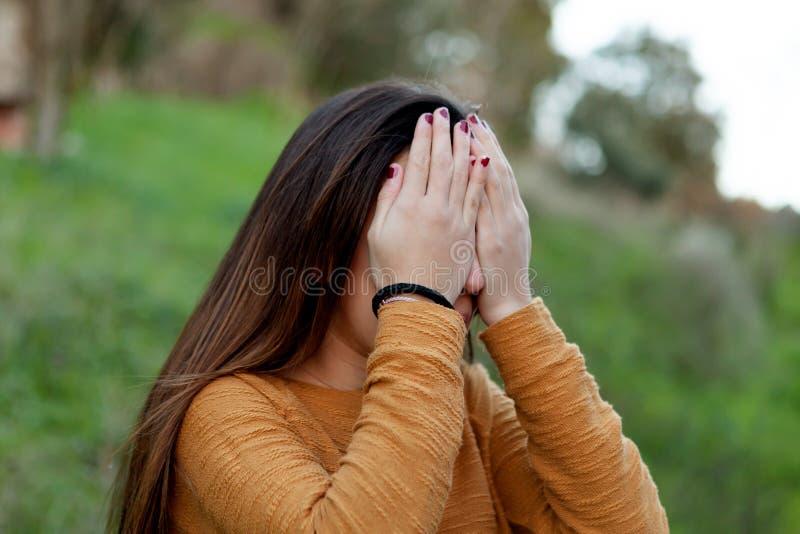 Ragazza dell'adolescente che copre il suo fronte fotografia stock