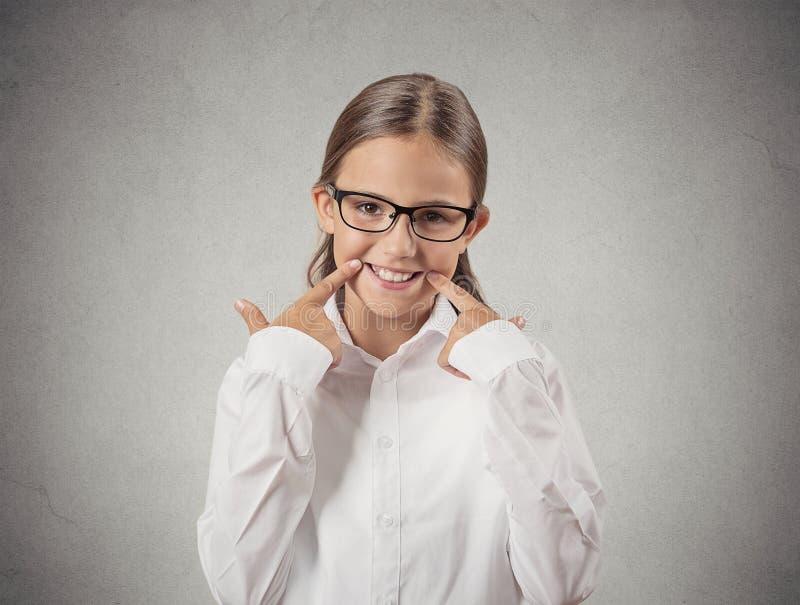 Ragazza dell'adolescente che fa il fronte sorridente di falsificazione fotografie stock