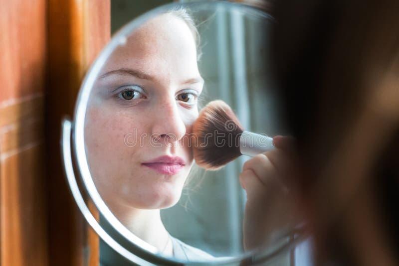 Ragazza dell'adolescente che guarda il suo auto in uno specchio che applica polvere a He immagine stock libera da diritti