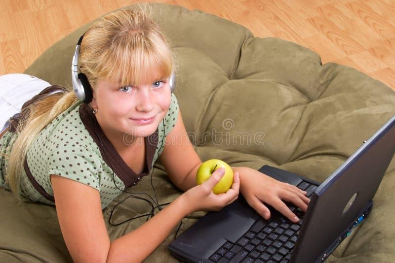 Ragazza dell'adolescente con il computer portatile immagini stock