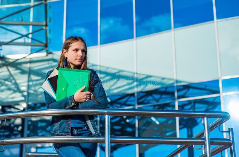 Ragazza dell'adolescente dello studente che tiene i libri ed i taccuini Ritratto all'aperto della ragazza castana del giovane ado fotografia stock libera da diritti