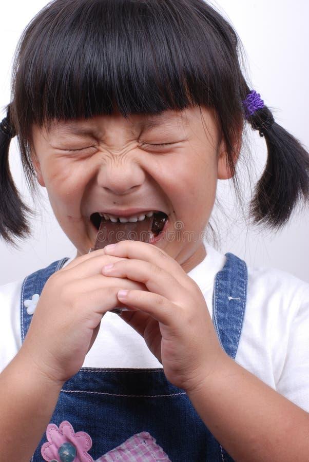Ragazza dell'Asia che mangia cioccolato immagine stock libera da diritti