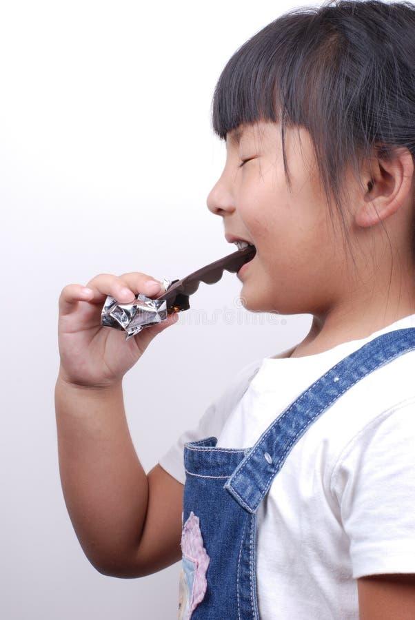 Ragazza dell'Asia che mangia cioccolato immagini stock