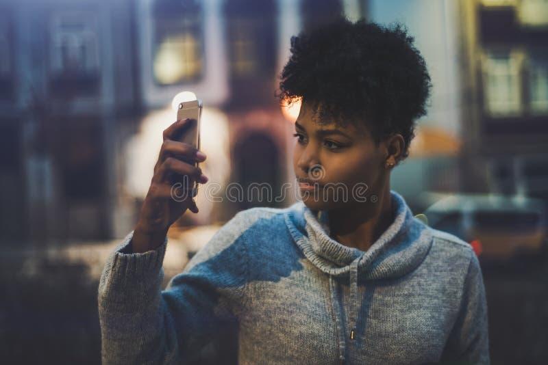 Ragazza dell'ebano che prende immagine sul cellulare alla notte fotografia stock libera da diritti
