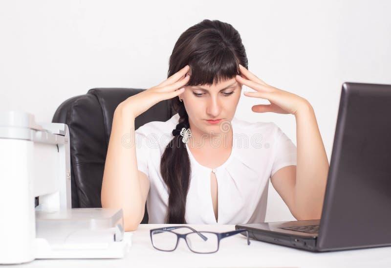 Ragazza dell'impiegato di concetto, donna di affari che tiene la sua testa un concetto dell'emicrania e dell'ansia dovute solleci fotografia stock