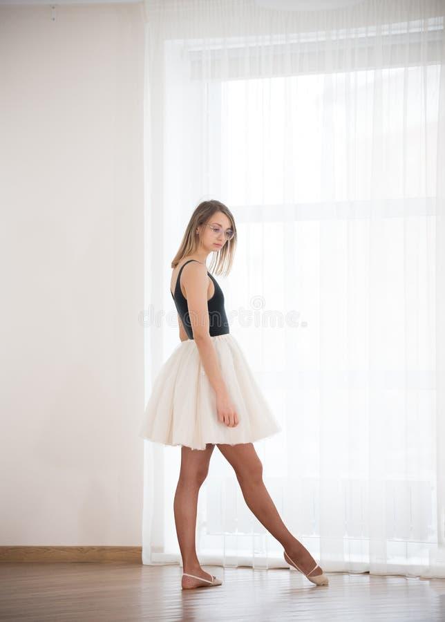 Ragazza della ballerina che sta allungante una gamba in avanti in uno studio di ballo immagini stock