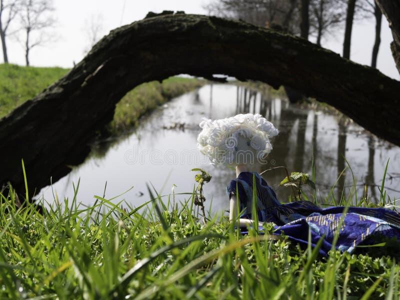 Ragazza della bambola di straccio con capelli bianchi che si siedono accanto ad un piccolo fiume immagini stock