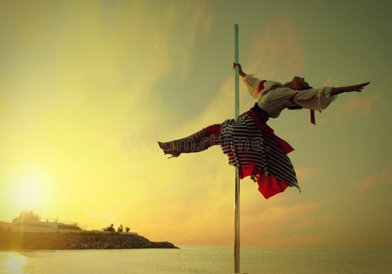 Ragazza della donna nel ballo del palo di esercizio del vestito contro il mare di tramonto. fotografia stock