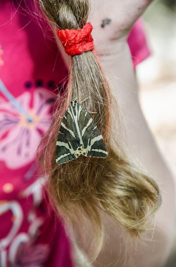 Ragazza della farfalla che si siede ai capelli immagine stock libera da diritti