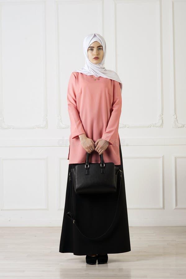 Ragazza della foto dello studio con l'aspetto orientale, in abbigliamento musulmano con una sciarpa sulla sue testa e borsa a dis immagini stock