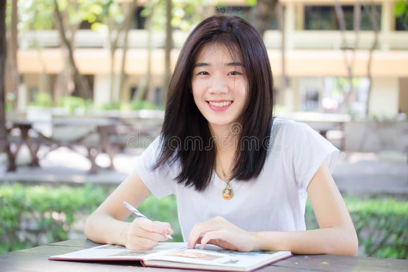 Ragazza della porcellana dell'Asia la bella dell'università tailandese dello studente scrive un libro immagine stock