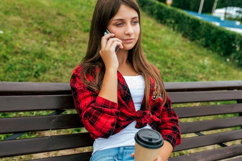 Ragazza della scolara di anni dell'adolescente 13-16 che si siede sul banco di estate in città dopo scuola, i genitori chiamano,  fotografia stock