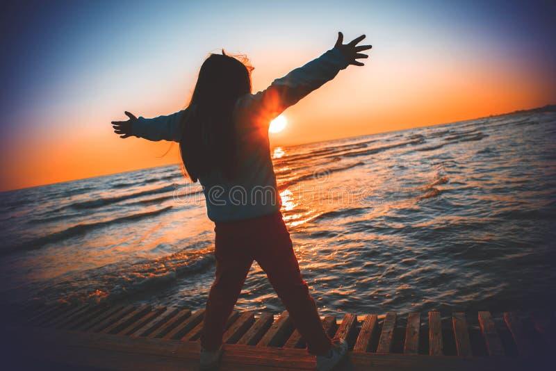 Ragazza della siluetta che solleva le mani sulla spiaggia nell'alba fotografia stock libera da diritti