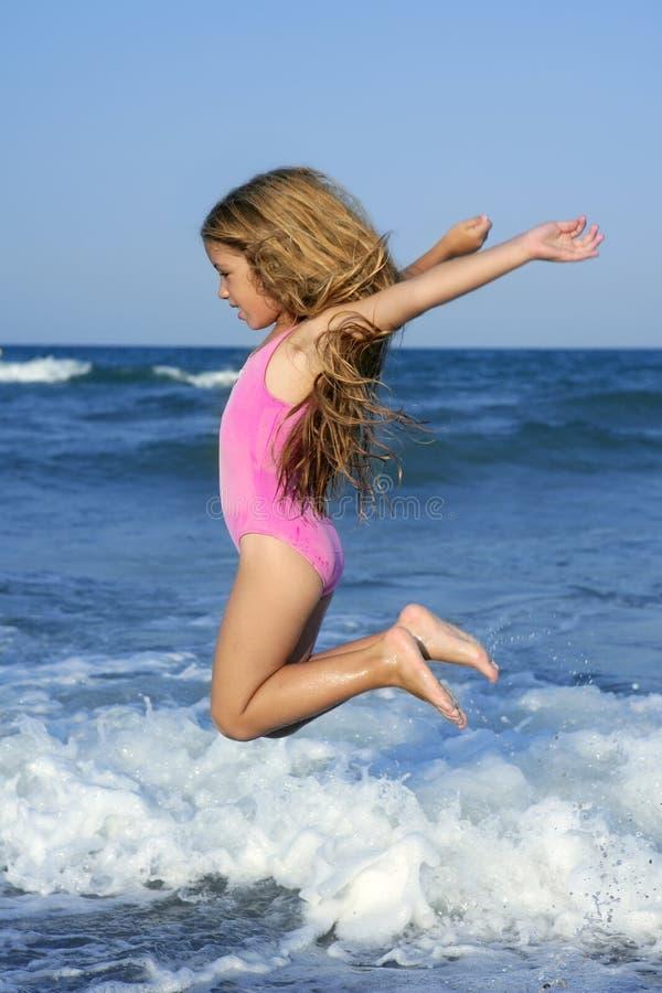 Ragazza della spiaggia di salto di volo nel puntello di mare blu immagini stock libere da diritti