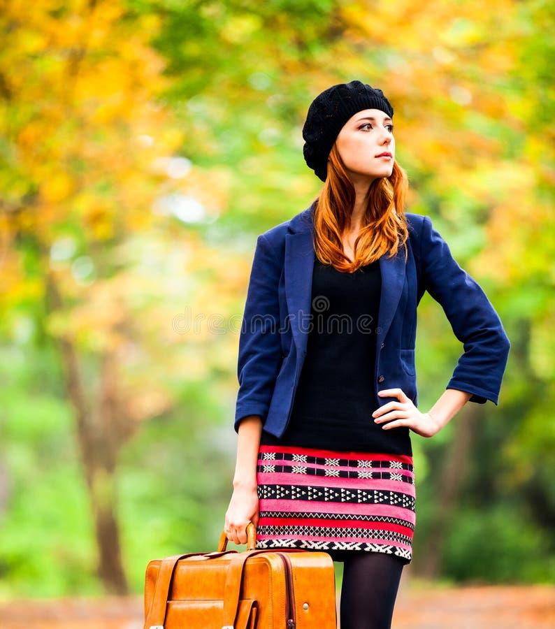 Ragazza della testarossa di stile in berretto, rivestimento e gonna con la valigia fotografie stock libere da diritti