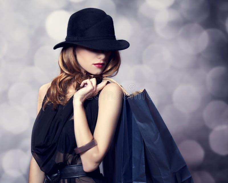 Ragazza della testarossa di stile con le borse di acquisto. fotografia stock libera da diritti