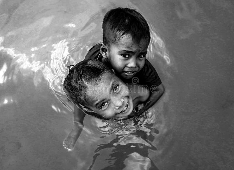 Ragazza della tribù di Bajau che porta suo fratello piccolo sulla sua spalla e che gioca in acqua, Semporna, Malesia fotografia stock libera da diritti