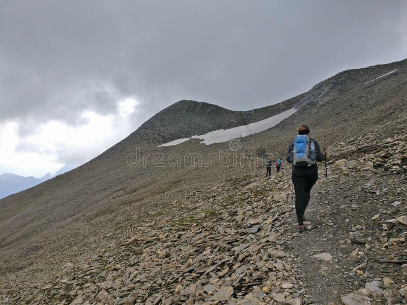 Ragazza della viandante che cammina su un campo di neve e della pietra nelle montagne con lo zaino fotografie stock