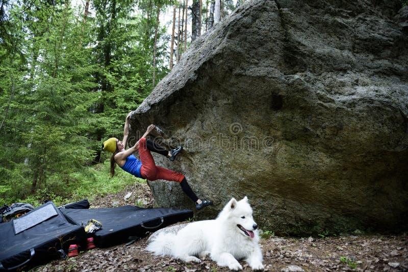 Ragazza dello scalatore su un masso Scalata estrema di sport Libertà fotografia stock
